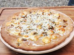 Bereiden: Verwarm de oven voor op 200°C. Maak het pizzadeeg: strooi de twee soorten bloem uit op een werkvlak en maak een kuiltje in het midden. Los de verse gist op in het lauwe water, voeg olijfolie en zout toe en giet bij de bloem. Kneed stevig tot een vast deeg en vorm een bolletje. Dek het deeg af met een keukenhanddoek en laat 90 minuten rijzen op warme plaats. Rol het deeg mooi dun en rond uit. Leg het op een ovenplaat.