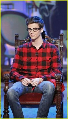 Grant Gustin embraces the nerd look with horn-rimmed glasses & checkered lumberjack shirt