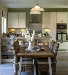 See how our interior designers bring our showhome kitchens to life. A natural wooden farm house table with earthy tones. #redrowhomes #kitchen #lighting