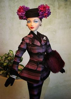 As Sandra Stillwell Presents opens her Toast of Manhattan event this weekend,MonolithicStudios darling Miss Gene Marshall shops for a new hat for her favorite cocktail suitGolden Gate Glamour convention Bandolier Morado is a luscious silk,tailored suit featuring alternating black and tonal lilac stripes.There was never any doubt that Miss Marshall would find the perfect hat:a delightful concoction of lilac and rose-colored flowers embellishing the little black matador-style hat from Spain…