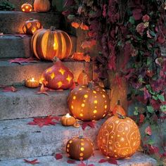 Pumpkins carved with stripes, dots, hearts and stars and lit with a candle for…