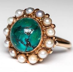 This lovely vintage turquoise cocktail ring features a centered large natural round cut cabochon of turquoise. The turquoise is beautiful with a nice textured appearance, and is surrounded by a halo of cream colored bezel set seed pearls. This ring is crafted of solid 14k yellow gold and is in good condition with some overall wear.