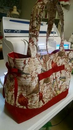 The pattern is Bow Tuck Tote; the quilter-seamstress got it at Amazon. The fabric is Winter Birds by Tim Coffey and she got it at Jo Ann's.