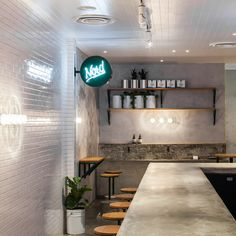 The thin footprint lent itself to using a long bar as the focal point; the feature has been constructed at the perfect height for customers to eat at but also allows visual access to the open kitchen where watching the food preparation becomes part of the overall experience...