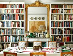 The dining room/library in Paris. The books are all from NYC and are arranged by subject; Carolina does not like her filing system messed with! The chairs are oak, 1940s Jansen, covered in a Carolina Irving Textile. In the mirror, the plates above the French doors are seen, along with the gunnera leaves over the mantel.