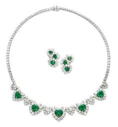 EMERALD <3 AND DIAMOND JEWELLERY   Comprising a necklace designed as five graduated diamond clusters, each centering upon a heart-shaped emerald, alternating with pear and brilliant-cut diamond v-shaped links, to the diamond line backchain, a pair of ear clips en suite, mounted in gold   Christie's