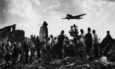 Citizens of Berlin stand amid rubble to watch an American C-47 cargo plane arrive with food & supplies, part of the Allied effort to counter a Soviet blockade of the city during the Berlin airlift, July 1948.