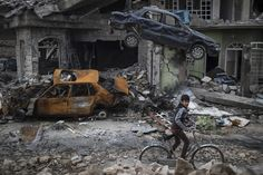 Mosul, Iraq  A boy rides his bike past bomb-damaged houses and wrecked cars in a neighbourhood recently liberated by Iraqi security forces in the western part of the city.