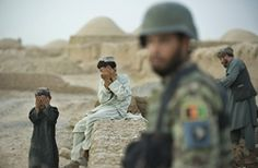 Two Afghan boys from the Pashtun tribe hide their faces from the camera as a soldier from the Afghan National Army (ANA)