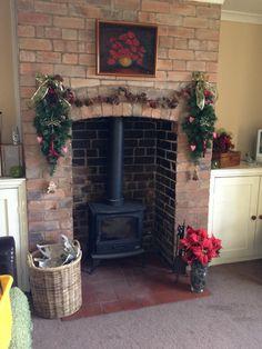Brick fireplace at Christmas with log burner