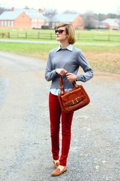 Ruby red skinny jeans, chambray shirt, gray sweater, and cognac loafers.