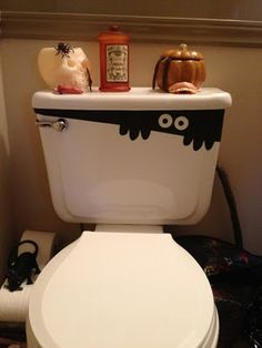 Cut scrap piece of black paper on an angle, cut out some fingers, and punch out the eyes.  Tape it onto the toilet! great for halloween