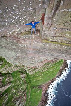 Daredevil Dave MacLeod perches on a rock face 1,000 feet up the world's hardest sea cliff climb. The Scotsman became the first person to freeclimb St John's Head on the Isle of Hoy, Scotland - widely believed to be the world's hardest sea cliff climb. He took time out half way up to check out the breathtaking views from a two-foot wide ledge.