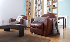 Ces fauteuils club en cuir ancien donne une touche vintage à cette pièce de vie au style contemporain.
