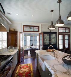 Beach style cottage via Town Plans, Peachtree City, GA.  Something about this kitchen draws me in .... maybe it's the warm wood with white or the marble counters or the colorful rug.