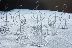 I would just make these. Wire Treble Clef Table Name Card Holder, Centerpiece for Wedding Reception, Place Card, Table Decoration for Special Occasion, Music Theme. $8.00, via Etsy.