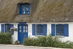Cottage with thatched roof, blue door and windows.