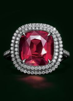 A double halo of diamonds surrounds a cushion-cut unenhanced ruby of over 6 carats in this platinum design.