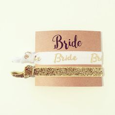 Dont let your hair get in the way on the dance floor! Every bride NEEDS a custom hair tie on their big day. Perfect for bachelorettes, showers and weddings, we offer hundreds of colors and prints to choose from so you can mix or match however youd like! The photos do not do these justice, the gold foil lettering is absolutely gorgeous on the white elastic.  Includes | 1 Favor Card (#9) 1 White + Gold Bride Hair Tie 1 Skinny Gold Glitter Hair Tie  See chart in photos for available card…