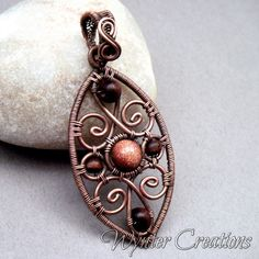 A sparkling brown goldstone bead sits surrounded by copper scrolls in this striking Renaissance inspired pendant. The frame and copper elements were carefully handcrafted from pure copper and joined with finer copper wire. Brown goldstone and dark wood beads were wrapped into the pendant, and the entire piece was antiqued and polished by hand to bring out all of the design details. The pendant measures 6.5 cm (appox. 2.5 inches) from the top of the handwoven bail to the bottom of the oval…
