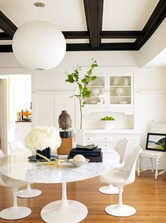 I say yes to the grandeur of a coffered ceiling  above a relaxed Knoll tulip table and chairs.
