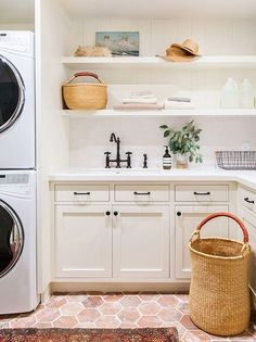 Woven baskets and weathered floor tiles give a new-build laundry room instant character.
