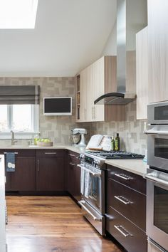 This midcentury kitchen is made in the details. With the stainless steel appliances, two-toned cabinets and a glass tile backsplash this functional and stylish space is perfect to entertain guests.