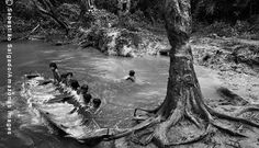 Crianças Awá esvaziam uma canoa para tentar se equilibrar durante um banho de rio (Foto Sebastião Salgado)