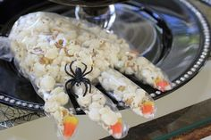 Witches' hands can be made by filling food handler gloves with popcorn. Use an almond or candy corn for fingernails, tie them off with a string, and add a spider ring to givethem that spooky touch. Source: Toni Spilsbury