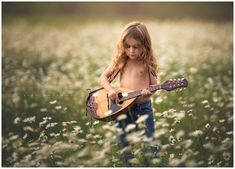 cute little boy with long curly hair plays a mandolin outdoors in a field of daisies during a photo session
