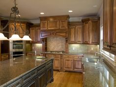 Granite counter kitchen with large island and rustic walnut cabinetry.