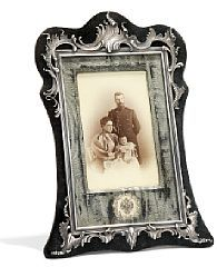 """Fabergé Rococo revival dark velvet and silver frame, cast with rocailles and scrolls, with a photograph of Tsar Nicholas II and Tsaritsa Alexandra Feodorovna of Russia and their firstborn, Grand Duchess Olga Nicolaevna. Passepartout with silk. Moscow 1896-1903. On the reverse of the frame a mark with text: """"Der Obersthofmeister I.K.H.D. Grossherzogin von Baden""""."""