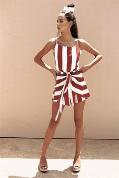 The striking Cherry Stripe Playsuit is made from a textured lightweight fabric with red and off white stripes throughout. It features a low back with tie up, thin straps, a high neckline and draping tie up feature across hips. For an effortlessly cute weekend outfit, paid with flat slides! By Sabo Skirt.