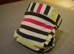 """Today I'm going to show you how I make my upcycled mock gDiaper cover. This tutorial features a size medium diaper.  For this project you will need:  *A large knit shirt (or knit/cotton interlock fabric) *One 1-1/4"""" sport knit elastic for waistbands *3/8"""" knit elastic for leg elastics *Snap tape -- these are compatible with the brand name liners and can be purchased here (the evenly spaced tape with 1 1/8"""" between each snap) *11"""" of hook and 5""""..."""