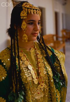 A young Bahraini girl wears a traditinal gold embroidered wedding dress, draped with necklaces, and an ornamental headdress. Leaves are knotted into the ends of her braids. Manama, Bahrain | © Adam Woolfitt/Corbis
