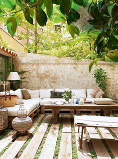 ChicDecó   Stylish Spanish courtyard with seating area built with pallets and decorated with raffia cushions and gorgeous wired lanterns