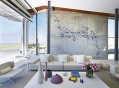 Living area looks out onto the ocean in Long Beach, New York. The room can be sealed from the elements by unfolding the 26-foot wide glass door seen at the top of the opening. [1306 × 979]