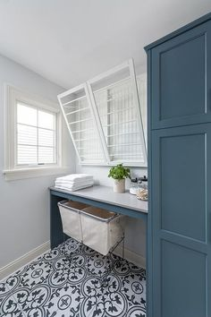 Side-by-side pull out drying racks are mounted in this well designed blue powder room and are positioned over a white quartz countertop fitted over vintage laundry carts placed on black and white quatrefoil tiles. Laundry Cart, Drying Rack Laundry, Laundry Closet, Laundry Hamper, Blue Laundry Rooms, Laundry Room Design, Mud Rooms, Vintage Laundry Rooms, Small Laundry