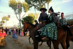 Young women riding side saddle behind their novios in flamenco dressing parading at La Feria de Abril de Sevilla, April 13, 2016.   Photo by Gerry Dawes©2016, Canon 5D Mark III, 24-105mm f/4 lens.