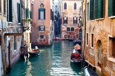 Beautiful colorful canal in Venice with parked gondolas near traditional architecture Italy