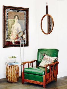 Antique reading nook with green chair and traditional artwork