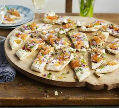 Smoked salmon flatbreads. Use a pizza base to create these little canapé-style nibbles with mascarpone, fish, red onion, dill and capers