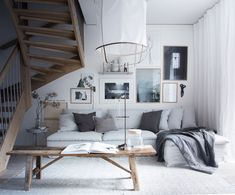 My Scandinavian Home's stunning layered yet minimalist living room | wall gallery adds a personal touch to the space | rustic wooden stool acts as a side table and the modern industrial lamp adds a graphic element | light grey linen sofa | IKEA Söderhamn sofa with a Bemz Loose Fit Urban cover in Silver Grey Rosendal linen