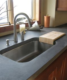 """the reveal — how much or little of the top of the sink is visible just below the inside edge of the countertop. I tend to prefer a no-reveal, or zero-reveal, look — just a smooth, straight drop from the countertop into the sink. You can also specify a """"negative reveal"""" where the countertop extends over the edge of the sink.  I think a slight negative reveal —⅛ inch or less — is fine."""