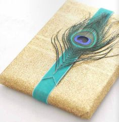 Peacock Feather embellishment on gift wrap.  I have to do something with all the left over feathers!!!