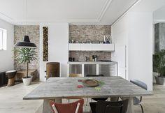 Tutta la brillantezza e la luce del bianco per l'ampia cucina e sala da pranzo di Re Use, appartamento di inizio Novecento ristrutturato nel 2014 da Global Architects, a L'Aia. Doppia armadiatura a incasso su misura e tavolo vintage