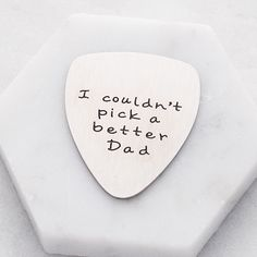 Engraved guitar pick in silver that states 'couldn't pick a better dad' made from tough and durable stainless steel. A wonderful keepsake and perfect gift