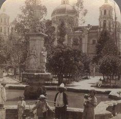 Un grupo de personas posan para la foto en el Jardín Juárez de la Villa de Guadalupe alrededor de 1900. Se aprecia la fuente construida en la época colonial que hoy ya no existe, y en el fondo, la fachada poniente de la antigua Basílica. Hoy este espacio es parte del nuevo templo, inaugurado en 1976.