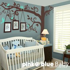 blue wall with tree and picture frames.  I love the idea of the hanging of the pictures...