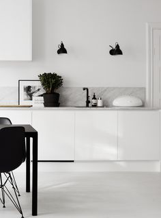 White kitchen with a marble backsplash and black accents. Via Stardust o sequins